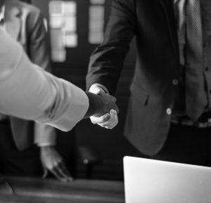 2 personas estrechándose la mano aceptando/realizando un acuerdo.